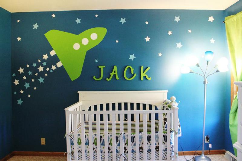 Mural de foguete e estrelas com nome do bebê acima do berço. As cores trazem contraste e alegram o quarto.